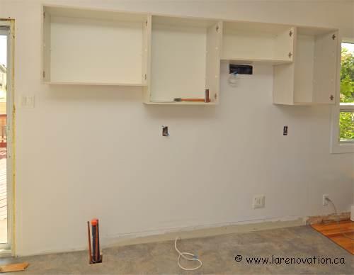 Pose des armoires au mur de cuisine